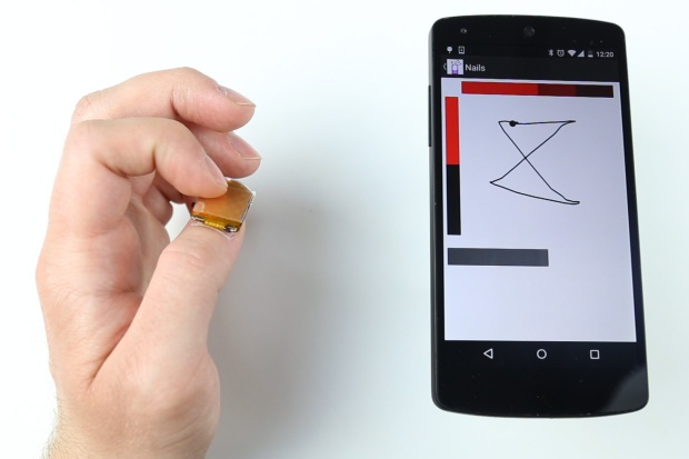 A new wearable device, NailO, turns the user's thumbnail into a miniature wireless track pad. Here, it works as a X-Y coordinate touch pad for a smartphone. Image courtesy of MIT Media Lab.